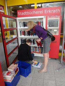 Die Leiterin und ein Mitarbeiter der Bücherei stellen neue Bücher in den Schrank